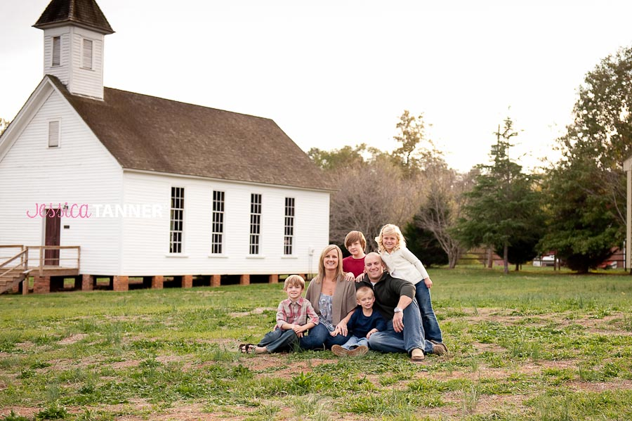 Family of 6 posing in front of a church