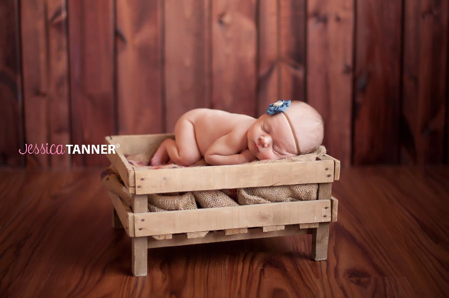 Newborn Baby Girl laying in vintage Crate